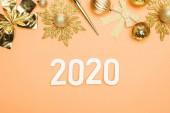 top view of 2020 számok közelében arany karácsonyi dekoráció narancs háttér