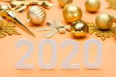 Photo white 2020 numbers near golden christmas decoration on orange background