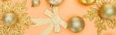 vrchní pohled na zlaté vánoční dekorace na oranžovém pozadí, panoramatický záběr