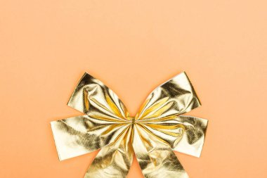 Top view of golden shiny decorative bow on orange background with copy space stock vector