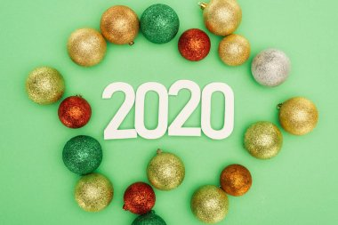 Top view of white 2020 numbers near multicolored Christmas baubles on green background stock vector