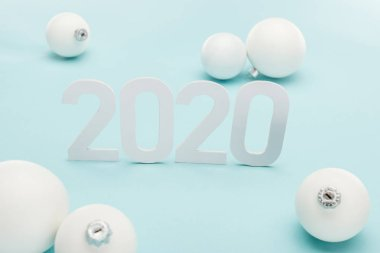 White 2020 numbers near Christmas baubles on light blue background stock vector