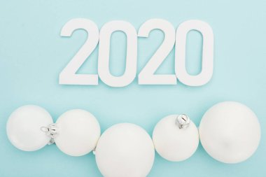 Top view of white 2020 numbers near Christmas baubles on light blue background stock vector
