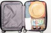 top view of travel bag with towel, cosmetic bag with bottles, clothes, sunglasses and hat on white background