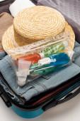 Reisetasche mit Kosmetiktasche mit Flaschen, Kleidung und Hut