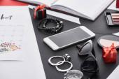 selective focus of calendar, eye shadow, gifts, smartphone, earrings and bracelets