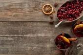 vrchní pohled na červeně kořeněné svařené víno s bobulemi, anýzem, pomerančovými plátky a skořicí na dřevěném rustikálním stole
