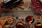 vrchní pohled na kus koláče, láhev a červeně kořeněné svařené víno s bobulemi, anýzem, pomerančovými plátky a skořicí na dřevěném venkovském stole