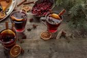 Fotografie roter Glühwein neben Tannenzweig, Beeren, Anis, Orangenscheiben und Zimt auf rustikalem Holztisch