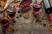 Fotografie roter Glühwein in der Nähe von Beeren, Anis, Orangenscheiben und Zimt auf rustikalem Holztisch mit Kopierraum