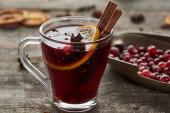 roter Glühwein mit Beeren, Anis, Orangenscheibe und Zimt auf rustikalem Holztisch