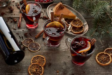 red spiced mulled wine near fir branch, pie, berries, anise, orange slices and cinnamon on wooden rustic table