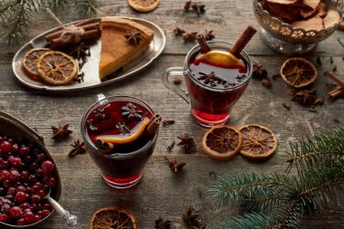 red spiced mulled wine near fir branch, pie, berries and spices on wooden rustic table