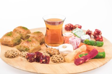 wooden board with delicious turkish sweets and tea isolated on white