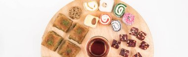 top view of wooden board with delicious turkish sweets and tea isolated on white, panoramic shot