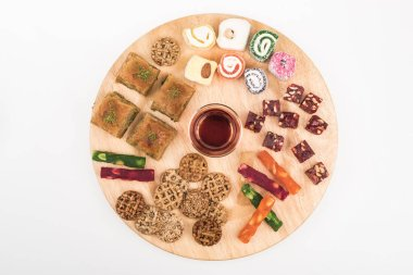 top view of wooden board with delicious turkish sweets and tea isolated on white