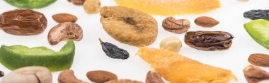 close up view of assorted nuts, dried fruits and candied fruit isolated on white, panoramic shot