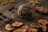 dried citrus and apple slices near ball of thread on wooden surface