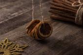sušené citrusové plátky na niti v blízkosti skořice a vločky na dřevěném pozadí