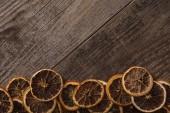 vrchní pohled na sušené oranžové plátky na dřevěném pozadí s kopírovacím prostorem