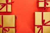 byt ležel se zlatými dárkovými krabicemi na červeném pozadí s kopírovacím prostorem