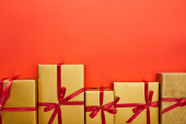 Photo flat lay with golden gift boxes on red background with copy space