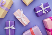 Photo top view of colorful presents with bows scattered on purple background