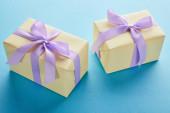 žluté barevné dárkové krabice s fialovými stuhami a luky na modrém pozadí