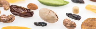 close up view of tasty assorted nuts, dried fruits and candied fruit isolated on white, panoramic shot