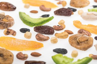 close up view of assorted nuts, dried fruits and candied fruit isolated on white