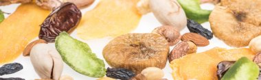 close up view of Turkish assorted nuts, dried fruits and candied fruit isolated on white, panoramic shot