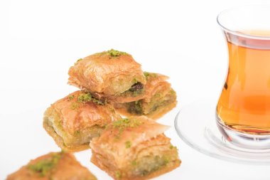 close up view of cup of tea near baklava isolated on white
