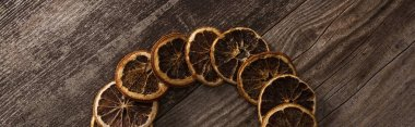 Top view of dried orange slices on wooden background, panoramic shot stock vector