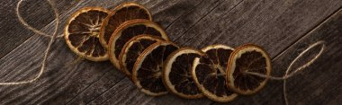 Top view of dried orange slices on rope on wooden surface, panoramic shot stock vector