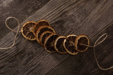 Top view of dried orange slices on rope on wooden surface stock vector