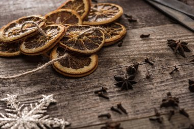 Dried citrus slices on rope near snowflake and anise on wooden surface stock vector