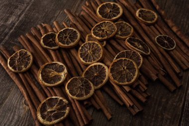 Dried orange slices and cinnamon on wooden background stock vector