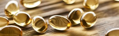 close up view of golden fish oil capsules scattered on wooden table, panoramic shot