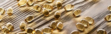 golden fish oil capsules scattered on wooden table, panoramic shot