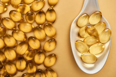 top view of golden shiny fish oil capsules in spoon on yellow background