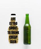 Draufsicht auf eine Flasche Bier in der Nähe von gepresstem Hopfen mit Leben ist zu kurz, um billiges Bier zu trinken Schriftzug isoliert auf weiß