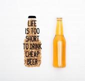 Draufsicht auf eine Flasche helles Bier in der Nähe von Vollkornschildern, Symbolen, Buchstaben, Schriftzügen, Illustrationen, Text, Inschrift isoliert auf weiß