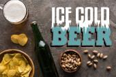 Draufsicht auf Schalen mit Pistazien und Chips in der Nähe von Flasche und Bierkrug auf grauer Oberfläche mit eiskaltem Bieraufdruck