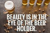 Draufsicht auf Flaschen und Glas helles Bier in der Nähe von verstreuten Pistazien auf grauer Oberfläche mit Schönheit liegt im Auge des Bierhalters Abbildung
