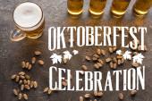 felső kilátás palack és üveg világos sör közelében szétszórt pisztácia szürke felületen Oktoberfest ünnepi felirat