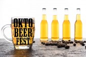 selective focus of glass with light beer and oktebeer fest lettering near bottles and coffee grains isolated on white