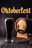 sklenice piva u malého soudku s kohoutkem a pšeničnými hroty na dřevěném stole s nápisem Oktoberfest