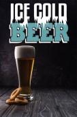 Glas frisches helles Bier neben gebratenen Zwiebelringen auf Holztisch mit eiskaltem Bier-Schriftzug