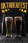 Gläser mit frischem hellen und dunklen Bier neben Flaschen auf Holztisch mit gelbem Oktoberfest-Schriftzug