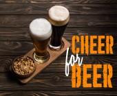 Gläser mit dunklem und hellem Bier neben Schüssel mit gerösteten Erdnüssen auf Holztisch mit Bier-Schriftzug